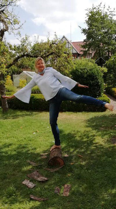 Frau balanciert auf Baumstamm