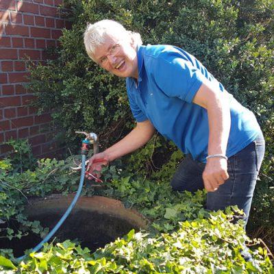 Christa befreit den Brunnen vom Efeu